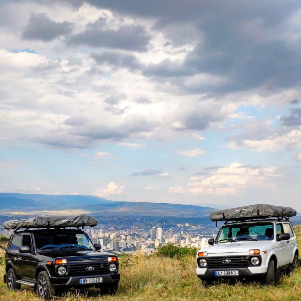 Two Lada Nivas with Tbilisi in the background